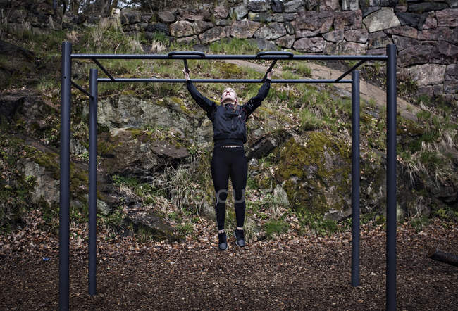 Full length of woman exercising on monkey bars at outdoor gym — Stock Photo