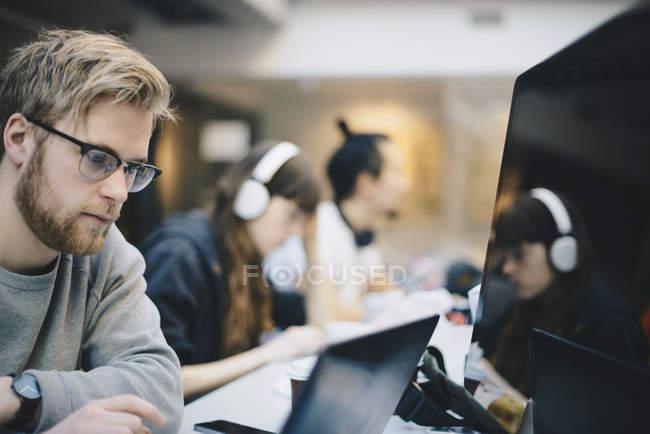 Mâle programmeur travaillant sur ordinateur avec ses collègues de bureau en bureau — Photo de stock