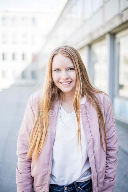 Ritratto di sorridente ragazza bionda in piedi contro edificio in città — Foto stock