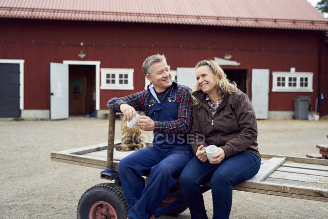 Couple holding mugs while sitting on old-fashioned trailer against barn — Photo de stock