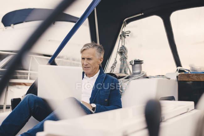 Hombre mayor usando el ordenador portátil mientras está sentado en el yate durante las vacaciones - foto de stock