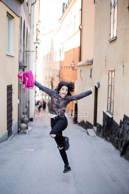 Full length of excited teenage girl jumping with backpack on street amidst buildings — Stock Photo