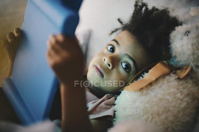 Retrato de niño con tableta digital mientras se está acostado con oso de peluche en la cama en casa - foto de stock