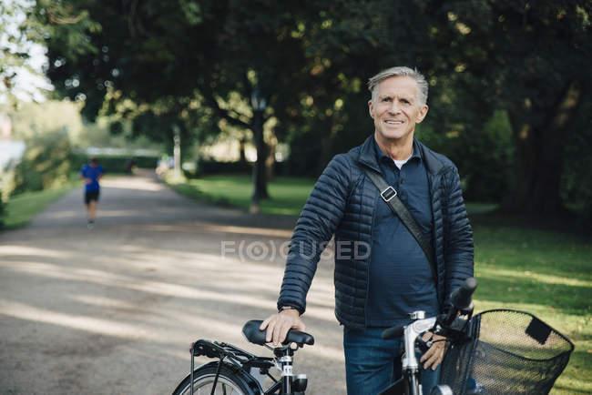 Ritratto di uomo anziano sorridente con bicicletta in piedi nel parco — Foto stock