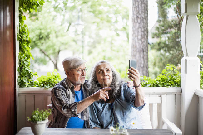 Senior couple taking selfie in porch - foto de stock