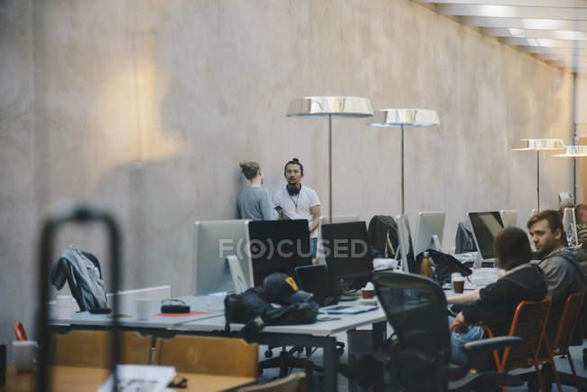Mâles et femelles de programmeurs/programmeuses discutant au bureau créatif — Photo de stock