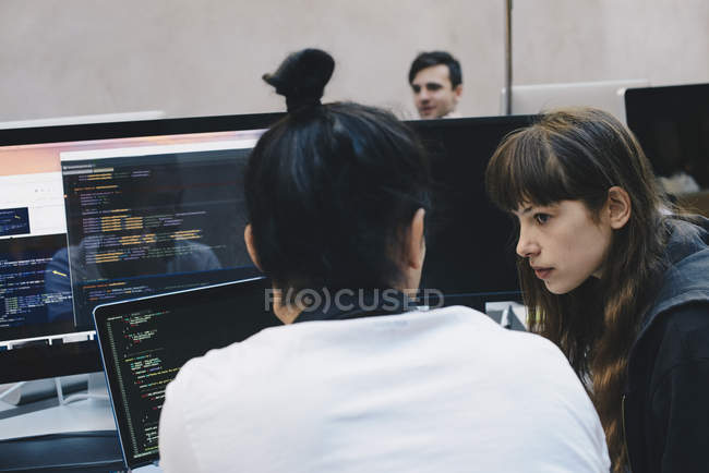 Male and female computer programmers discussing at office desk — Stock Photo