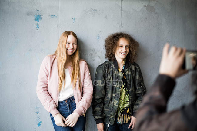 Cropped image of teenage girl photographing friends standing against wall at parking garage — Stock Photo