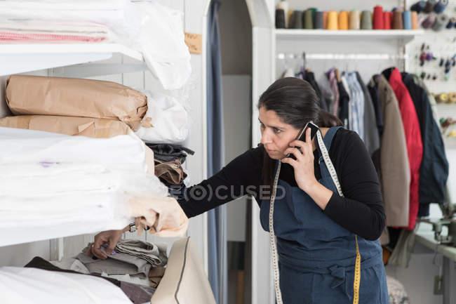 Доросла самотня суха чистка розмовляє на смартфоні під час роботи в Ландромат. — стокове фото