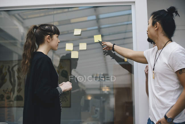 Male programmer explaining adhesive note to female colleague in office — Stock Photo