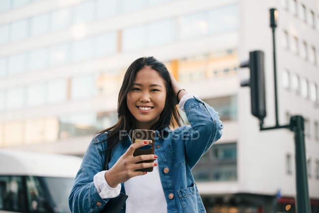Retrato de una adolescente sonriente usando un teléfono inteligente contra un edificio en la ciudad - foto de stock