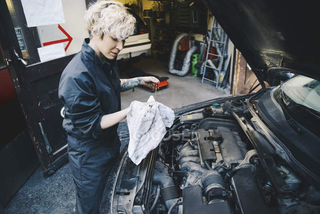 Side view of female mechanic checking oil with dipstick outside auto repair shop — Stock Photo
