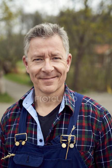 Портрет улыбающегося фермера, стоящего на ферме — стоковое фото
