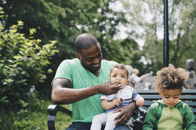 Smiling father feeding baby boy while sitting with son on bench at park — Stock Photo