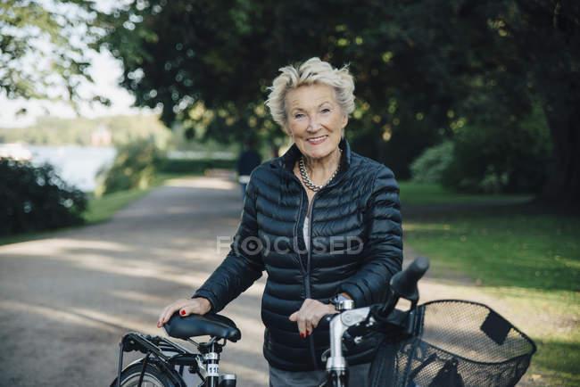 Портрет улыбающейся пожилой женщины с велосипедом в парке — стоковое фото
