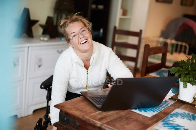 Portrait of smiling disabled woman using laptop at table in house — Stockfoto