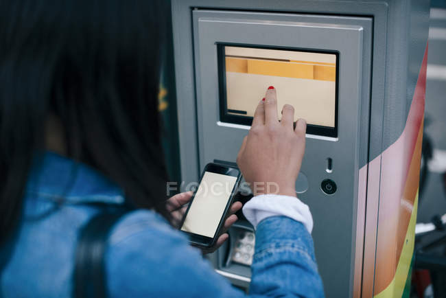 Vue arrière de l'adolescente touchant l'écran ATM tout en tenant le téléphone intelligent — Photo de stock