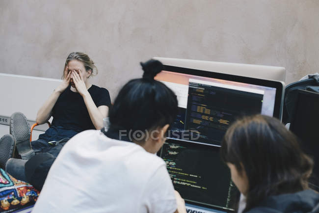 Male and female computer programmers using computer at office — Stock Photo