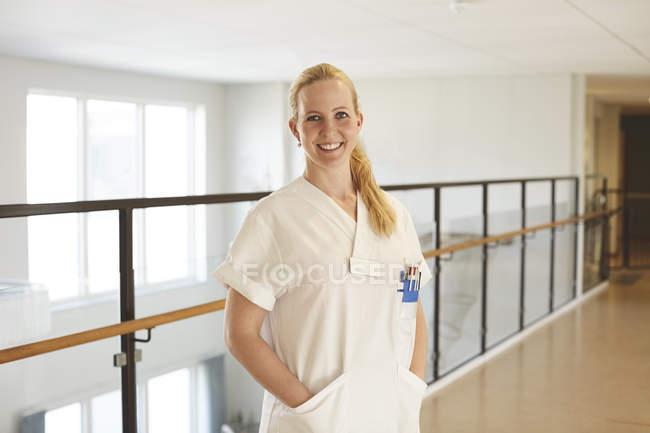 Retrato de enfermeira sorridente em pé com as mãos nos bolsos no corredor do hospital — Fotografia de Stock