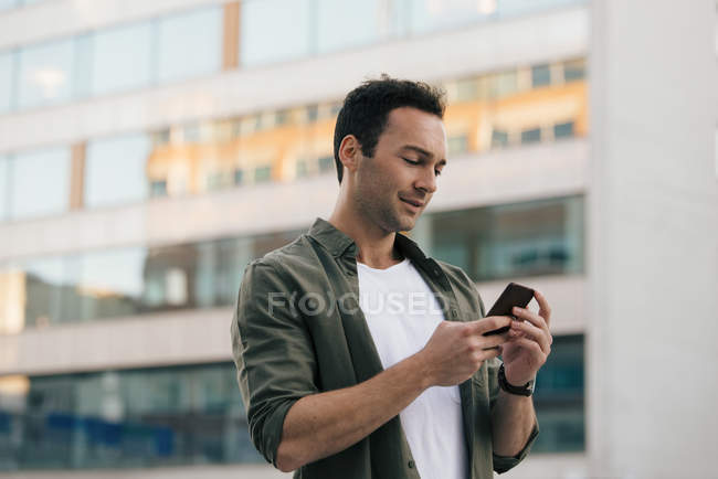 Low angle view of man using smart phone while standing against building in city — Stock Photo