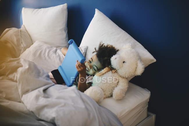 Vista de ángulo alto de niño acostado con peluche durante el uso de tabletas digitales en cama en casa - foto de stock