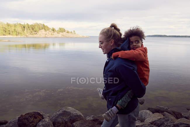 Seitenansicht der jungen Mutter geben Huckepack auf den Sohn am Seeufer — Stockfoto