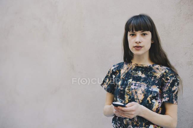 Ritratto di programmatore di computer donna fiduciosa che tiene lo smartphone mentre si trova contro la parete beige in ufficio — Foto stock