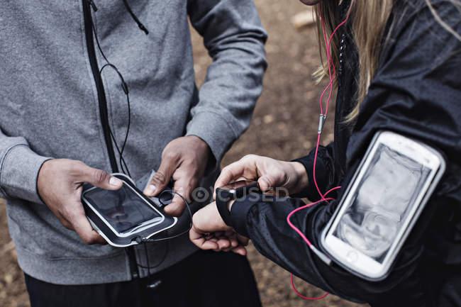 Животик спортсменов, используя смарт-часы и мобильный телефон в лес. — стоковое фото