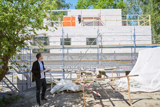 Повна довжина архітектора з кресленням, що дивиться на незавершену будівлю. — стокове фото