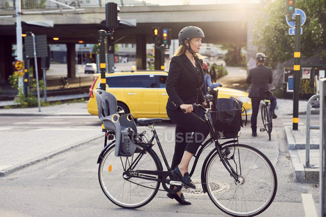 Mature businesswoman with bicycle on street in city — Stock Photo