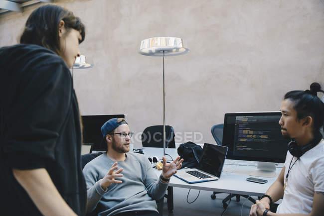 Программист, gesturing при обсуждении плана с коллегами в офисе творческих — стоковое фото