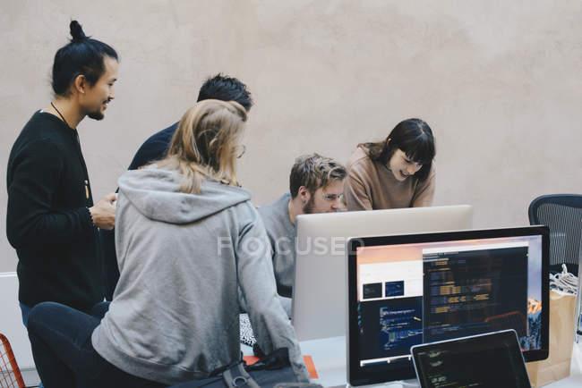 Mâles et femelles les programmeurs à l'aide de Pc de bureau en bureau créatif — Photo de stock