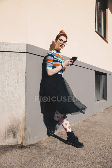 Full length of young woman using mobile phone while standing by wall — Stock Photo