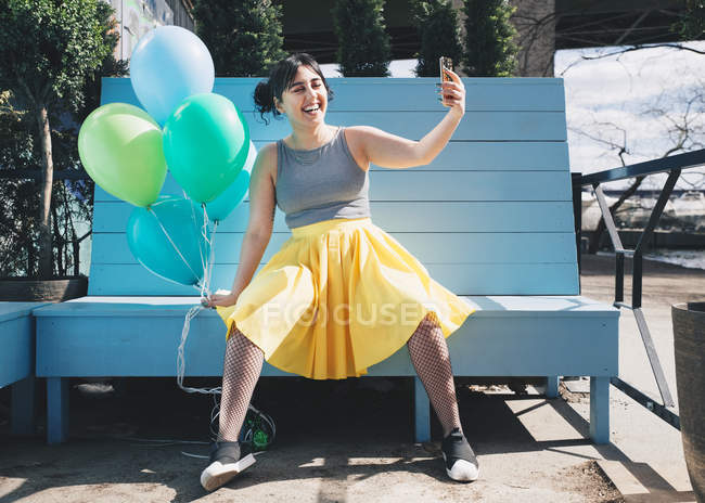 Happy young woman taking selfie with balloons while sitting on bench — Stock Photo