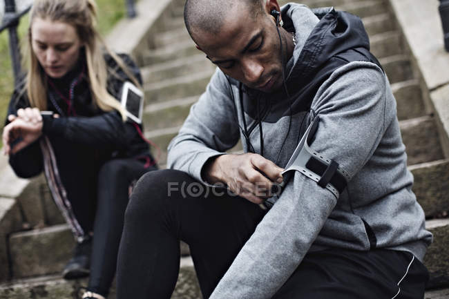 Mid adult man wearing smart phone on arm while woman checking time in background on steps — Stock Photo