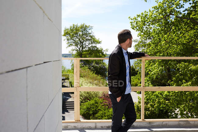 Thoughtful businessman standing at balcony on sunny day — Stockfoto