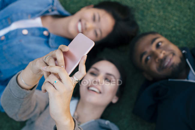 High angle view of smiling young woman taking selfie with friends while lying down on grass — Foto stock