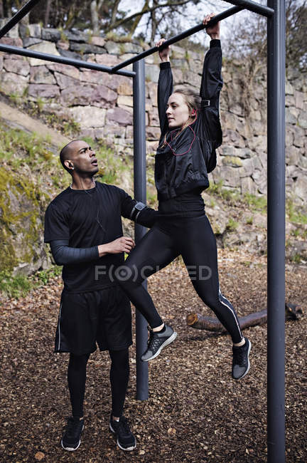 Mid adult man assisting woman exercising on monkey bars in forest — Stock Photo