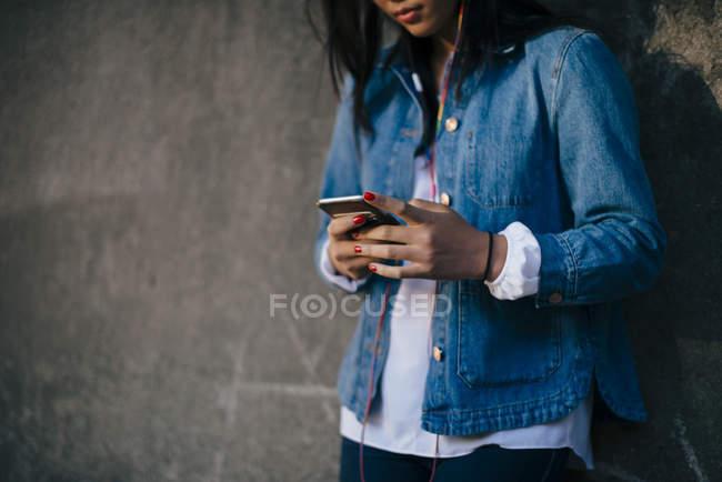 Sezione centrale della ragazza adolescente utilizzando il telefono cellulare contro il muro — Foto stock