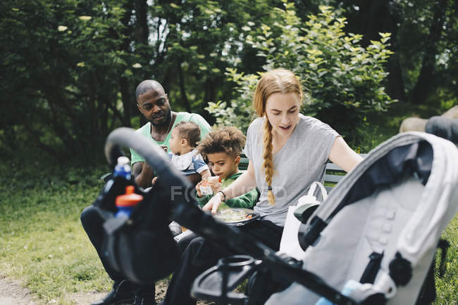 Parents and children sitting on bench against trees at park — Stock Photo