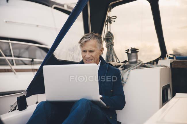 Homem sênior usando laptop enquanto sentado em iate — Fotografia de Stock