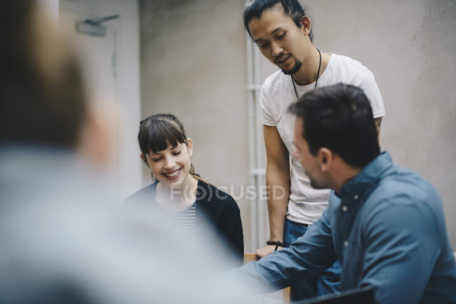 Multi-ethnic computer programmers discussing in office — Stock Photo