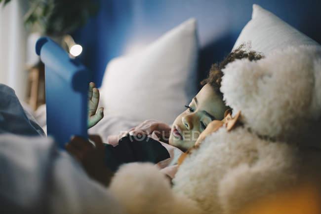 Niño tumbado con oso de peluche mientras está usando la tableta digital en cama en casa - foto de stock