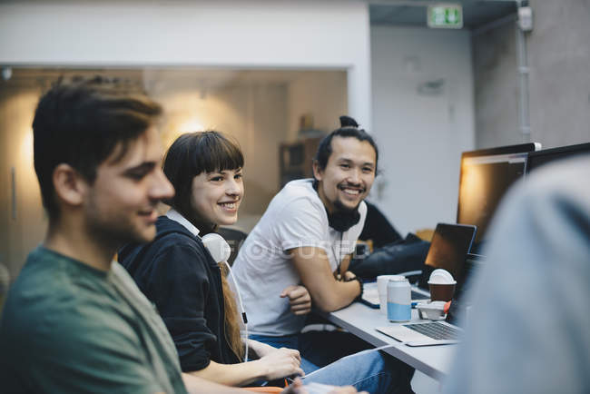 Happy male and female computer programmers talking at desk in office — Stock Photo