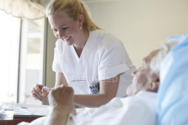 Happy female nurse giving cough syrup to senior man in hospital ward — Stock Photo