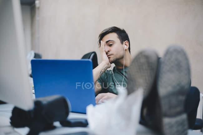 Programador de computador cansado usando laptop enquanto sentado com os pés na mesa no escritório — Fotografia de Stock