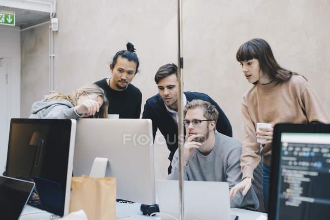 Des jeunes informaticiens à l'aide de Pc de bureau à bureau bureau créatif — Photo de stock