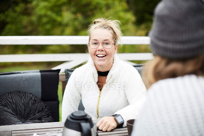 Smiling disabled woman looking at male caretaker sitting at table in backyard — Stock Photo