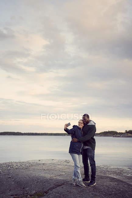 Улыбаясь пара принимая selfie стоя на пляже против неба на закате — стоковое фото
