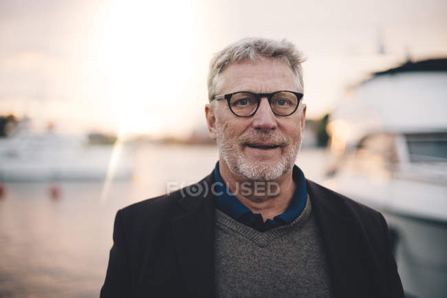 Portrait of senior man smiling at harbor during sunset — Stock Photo